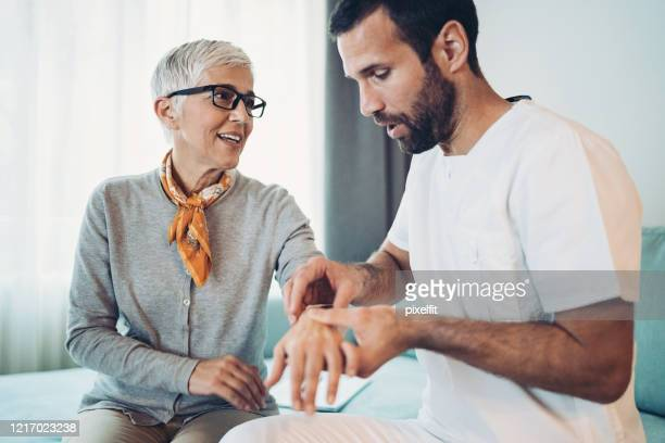 doctor examining senior woman's arm and wrist - rheumatoid arthritis stock pictures, royalty-free photos & images