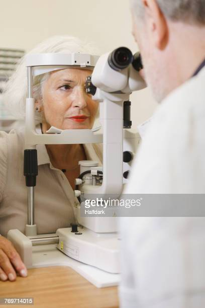 Doctor examining senior womans eye at clinic