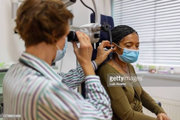 doctor examining the ear of a senior woman in clinic - infectious disease stock pictures, royalty-free photos & images