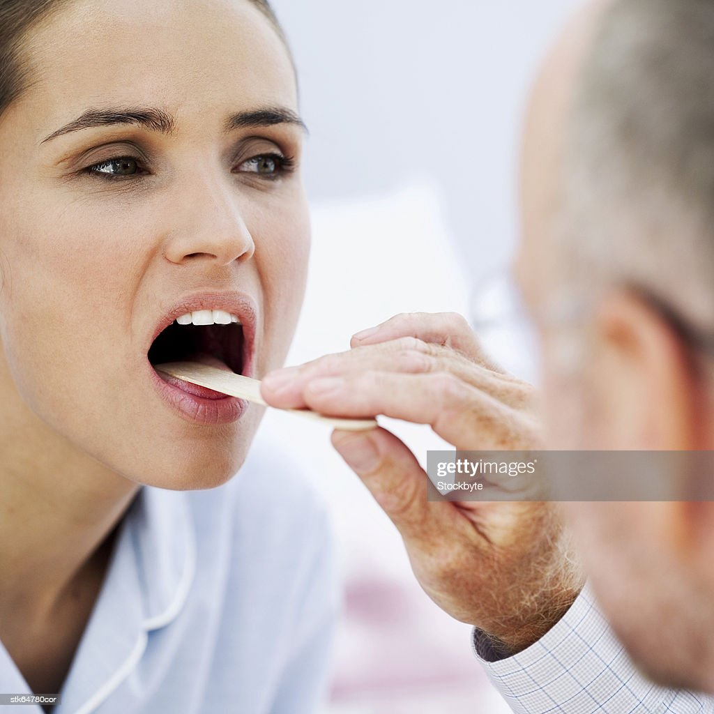 doctor examining with a woman with a tongue depressor : Stock Photo