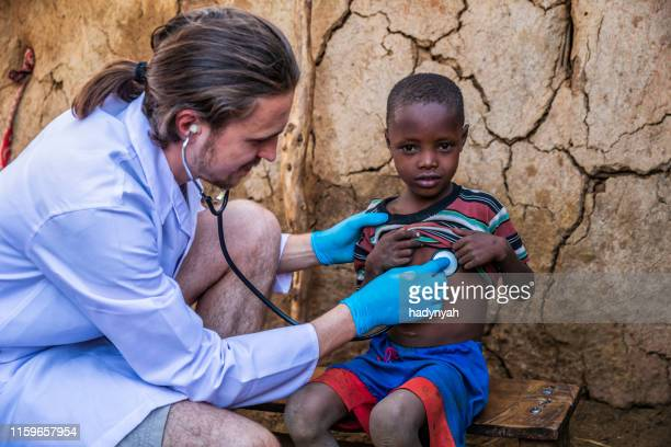 doctor examining young african boy in small village, kenya - charity and relief work stock pictures, royalty-free photos & images