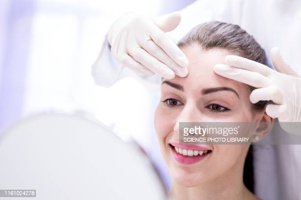 doctor examining young woman's forehead - human skin stock pictures, royalty-free photos & images