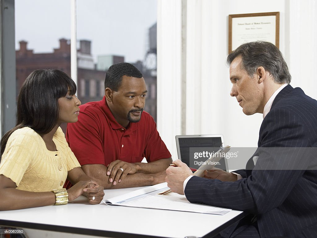 Doctor Explaining a Document to a Couple at His Clinic : Stock Photo