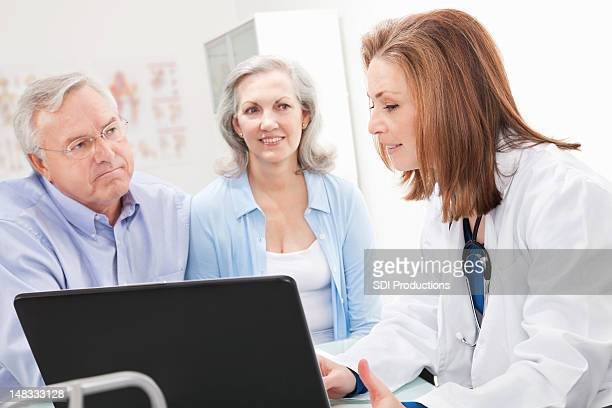 Doctor explaining Medical News to Senior Adult Patient and Spouse