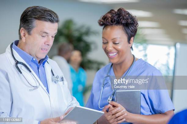 doctor explaining medical results on digital tablet to nurse - civilian stock pictures, royalty-free photos & images
