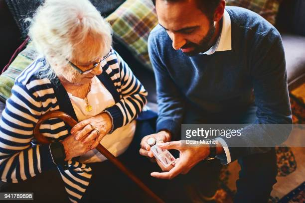 doctor explaining medicine dosage to senior patient - caregiver stock pictures, royalty-free photos & images