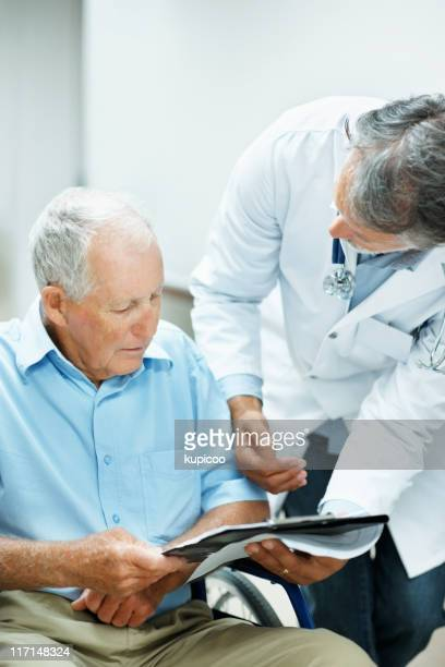 Doctor explaining reports to a disabled man
