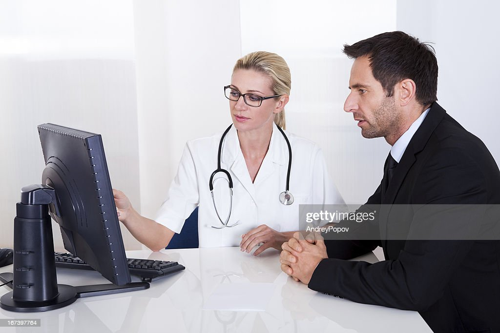 Doctor explaining something to a male patient : Stock Photo