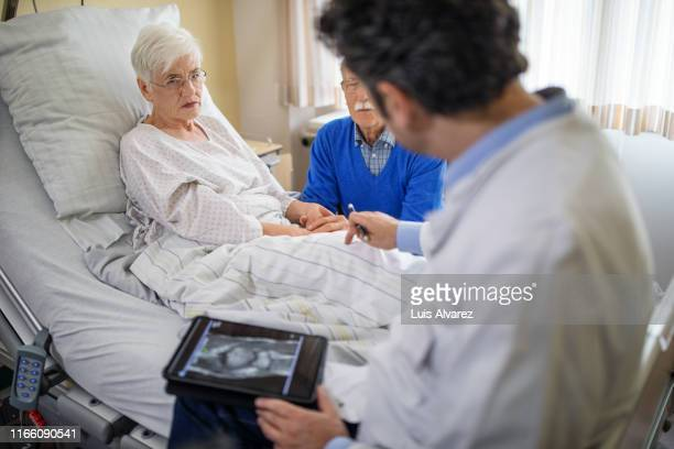 doctor explaining the knee replacement treatment to senior patient - knee replacement surgery stock pictures, royalty-free photos & images