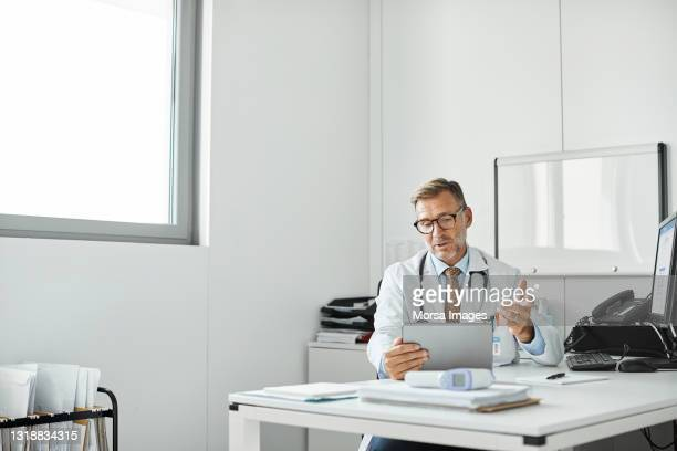 doctor explaining through video call in clinic - healthcare stock pictures, royalty-free photos & images