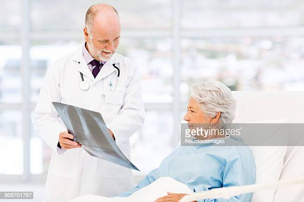 Doctor Explaining X-Ray Results To Female Patient