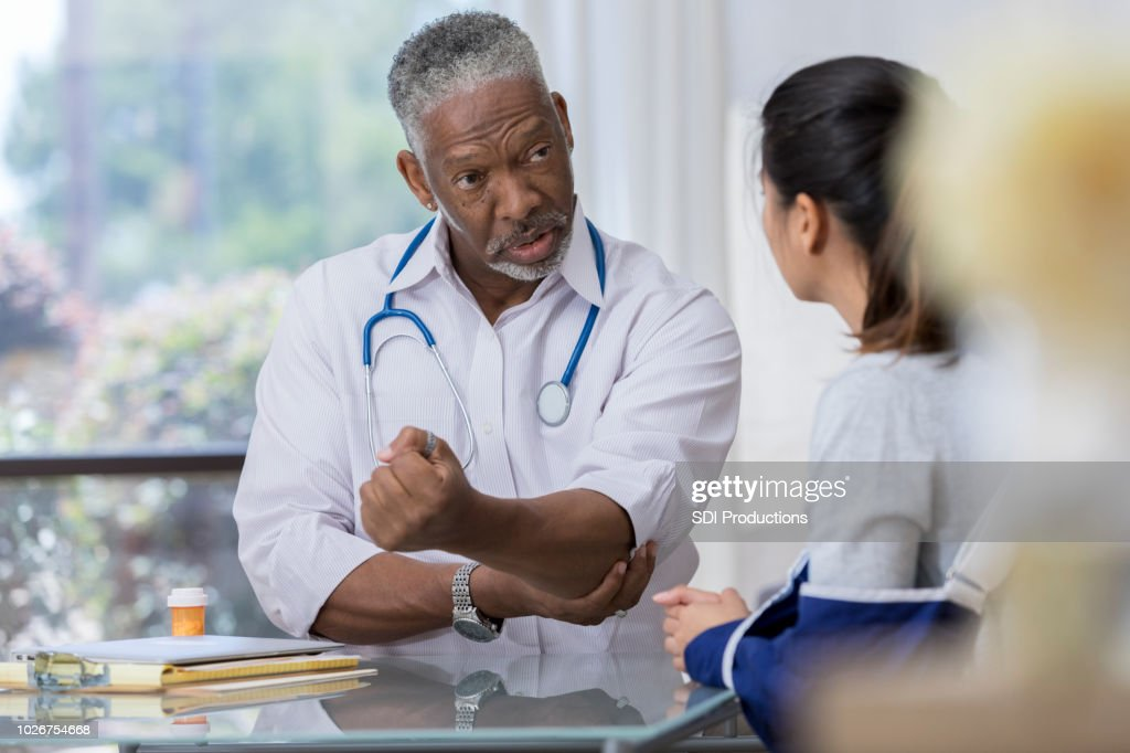 Doctor explains injury to patient : Stock Photo