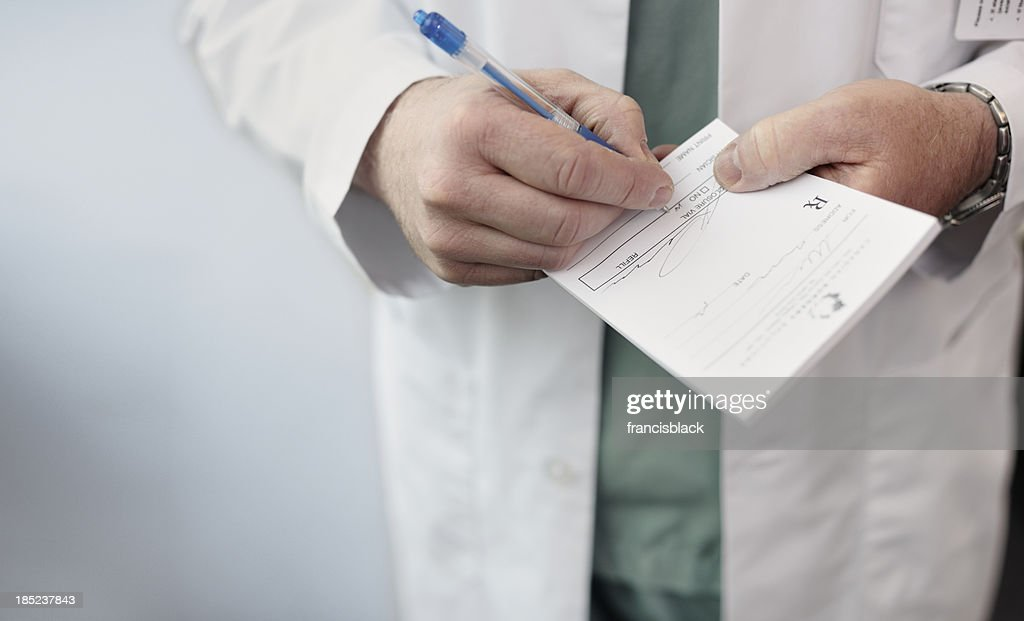 Doctor filling out a prescription : Stock Photo