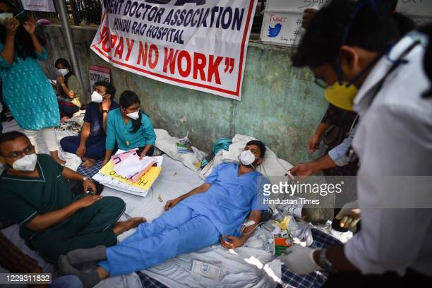 Doctor from Hindu Rao Hospital rests after his blood sugar levels dropped while sitting in protest over the non-payment of salaries, on October 27,...