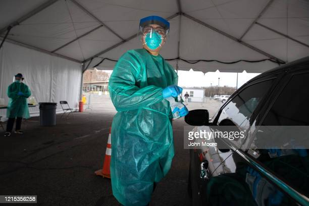 A doctor from SOMOS Community Care prepares to test a patient at a drivethru testing center for COVID19 at Lehman College on March 28 2020 in the...