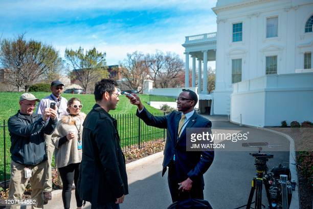 A doctor from the White House Physicians Office checks temperatures on a journalist outside the Brady Press Briefing Room prior to a press conference...