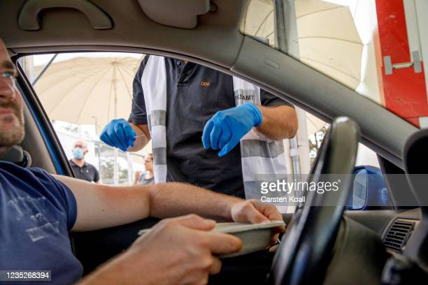 Doctor gives a dose of the Moderna vaccine to the driver of a car in a drive-in vaccination station in an IKEA car park on the third day of the...