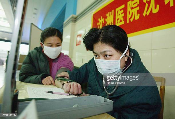 A doctor gives a medical check to a passenger in a medical center at a railway station on January 25 2005 in Shenyang of Liaoning Province China The...