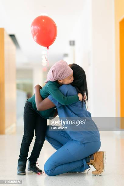 doctor gives a red balloon to a little girl with cancer - red alert 2 stock pictures, royalty-free photos & images