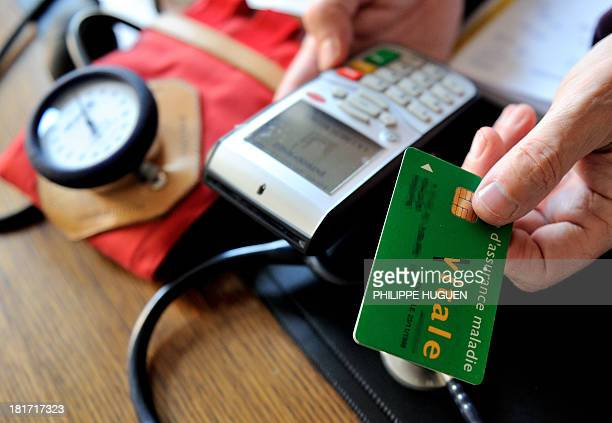 A doctor gives back a French health insurance electronic card after using it in a connected reader on September 23 2013 in Godewaersvelde northern...