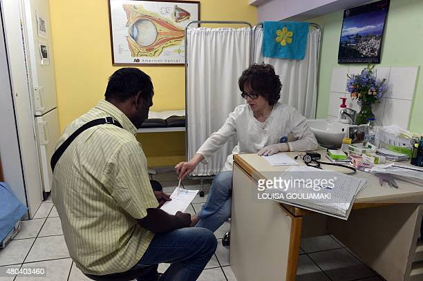 A doctor gives instructions to a migrant patient at a Doctors of the World medical center and a shelter for migrants and uninsured Greeks in Athens...
