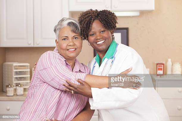 Doctor gives senior adult patient hug at clinic.