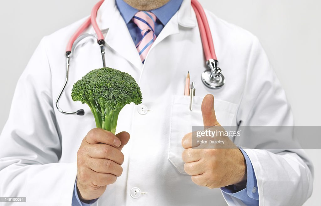 Doctor gives thumbs up to a floret of broccoli : Stock Photo