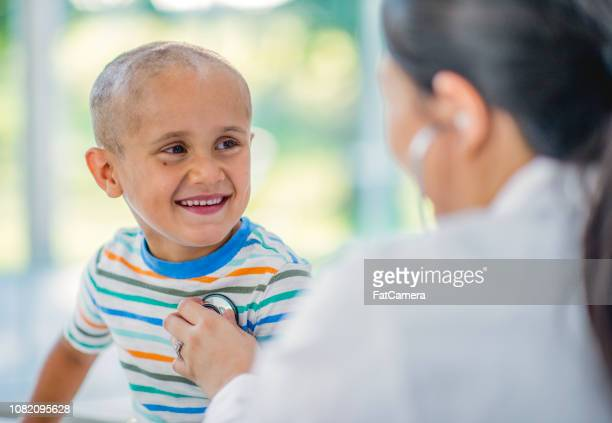 Doctor giving a boy with cancer a check up