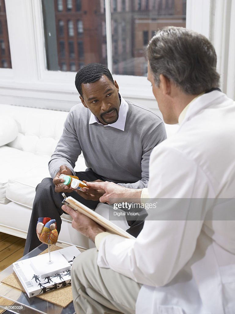 Doctor Giving an Explanation About the Medicine Given to a Male Patient : Stock Photo