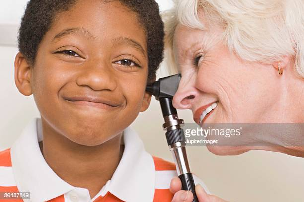 doctor giving boy ear exam - ear exam stock photos and pictures