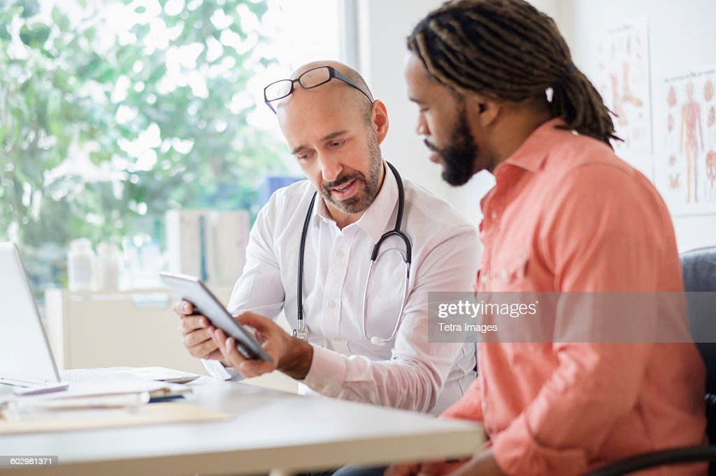 Doctor giving consultation to patient using digital tablet : Stock Photo