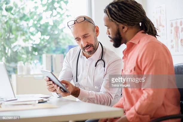 doctor giving consultation to patient using digital tablet - male doctor stock photos and pictures