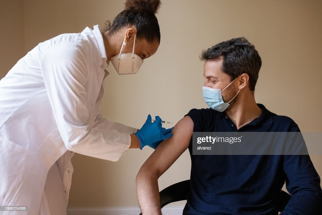 Doctor giving covid-19 vaccine to a man : Stock Photo