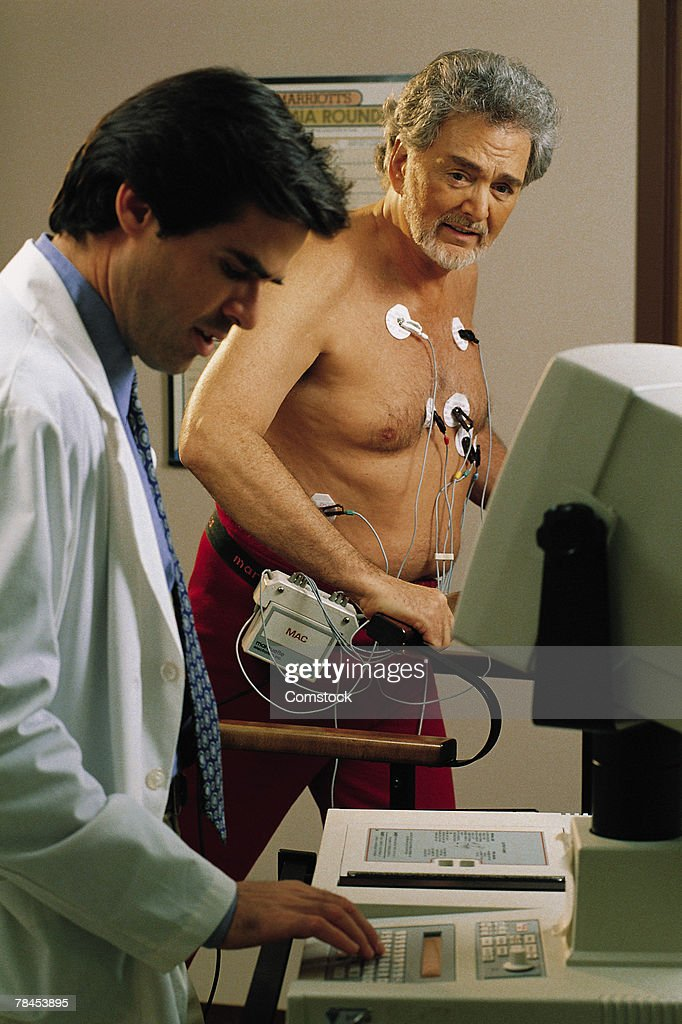 Doctor giving mature man a stress test : Stockfoto