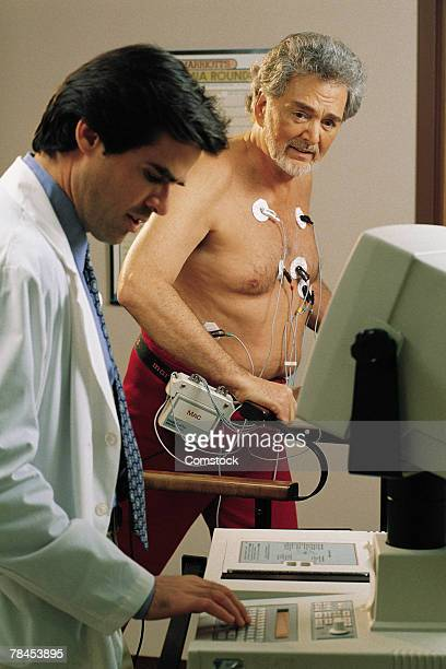 doctor giving mature man a stress test - stress test stock pictures, royalty-free photos & images