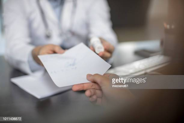 doctor giving patient a note - geben stock-fotos und bilder