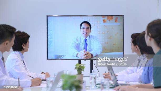doctor giving presentation through video conference while colleagues sitting on table - film and television screening stock-fotos und bilder