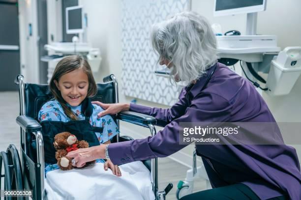 doctor giving teddy bear to girl in wheelchair - bewogen beeldtechniek stockfoto's en -beelden