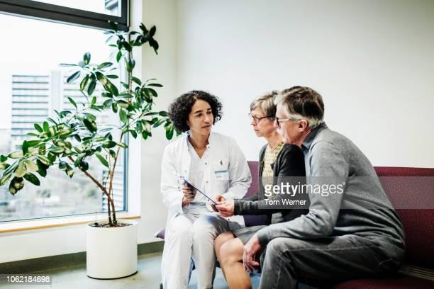 doctor giving test results to elderly couple - disruptaging stock-fotos und bilder