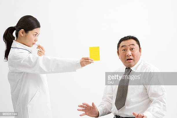 doctor giving yellow card to a patient - metabolic syndrome stock pictures, royalty-free photos & images