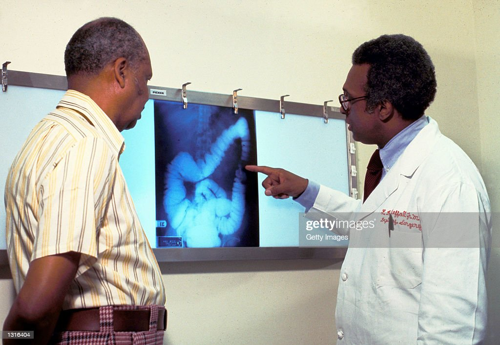 A doctor goes over a patient''s x-ray, screening for colon cancer. There is no single cause of colon cancer. Cancer of the colon and rectum accounts for 15% of cancer deaths.