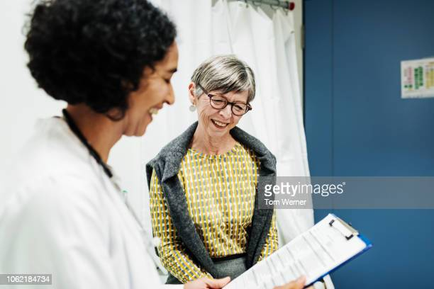 doctor going over test results with patient - dokter stockfoto's en -beelden