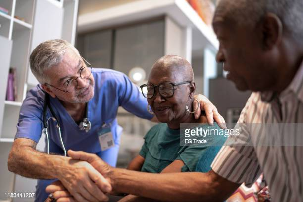 doctor greeting a senior couple - patience stock pictures, royalty-free photos & images
