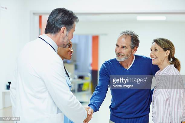 Doctor greeting couple in hospital