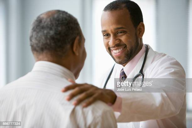 doctor greeting patient - hand on shoulder stock photos and pictures