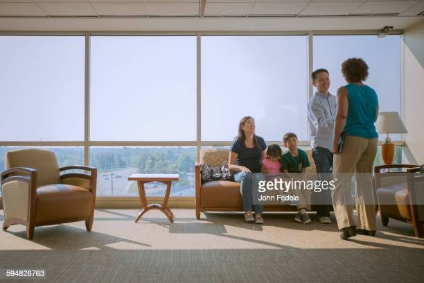 doctor greeting patients in waiting room - patients brothers stock pictures, royalty-free photos & images