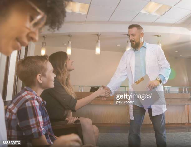 Doctor greeting patients in waiting room with hand shake