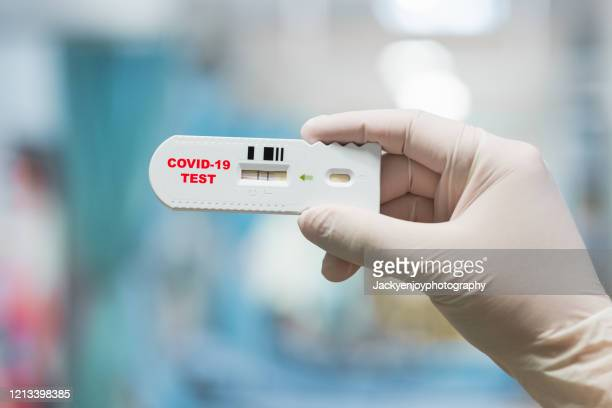 doctor hand holding positive coronavirus or covid-19 rapid test - scientific experiment stock pictures, royalty-free photos & images
