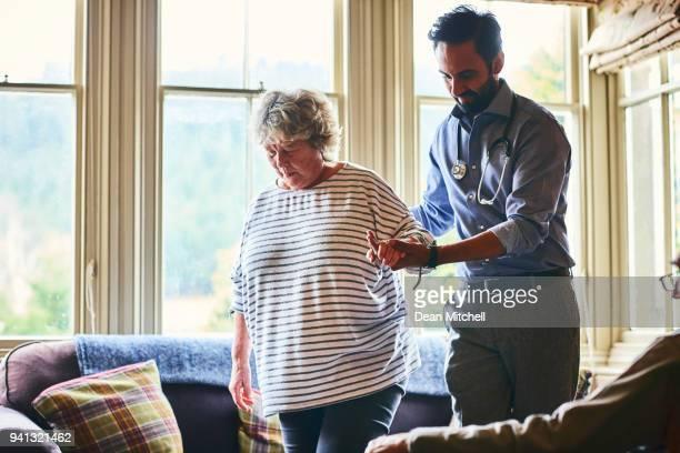 Doctor helping elderly female patient to walk