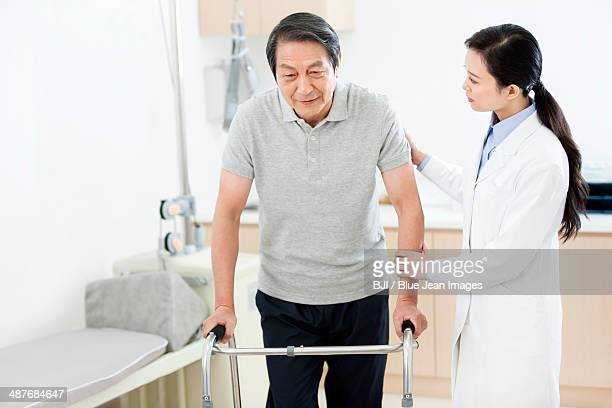 Doctor helping patient with walker